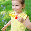Portrait of little girl blowing soap bubbles — Stock Photo