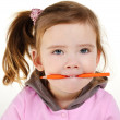 Portrait of cute little girl holding a pencil in teeth — Stock Photo #9538745