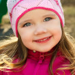 Portrait of smiling little girl outdoors on a spring day — Stock Photo #9947044