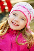 Portrait of smiling little girl outdoors on a spring day — Stok fotoğraf