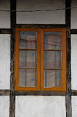 Orange latticed window with brown framework — Stock Photo