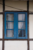 Blue latticed window with curtain and brown framework — Stock Photo