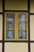 Yellow latticed window with curtain and brown framework — Stock Photo
