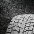 Studio close-up detail of winter tire tread full of snow - Stock Photo