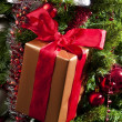 Stock Photo: Red ribboned gift on christmas tree