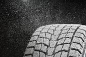 Studio close-up detail of winter tire tread full of snow — Stock Photo