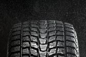 Studio close up of wet winter tire tread in the rain — Stock Photo