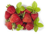 Basket of fresh strawberries with its leaves (isolated on white) — Stock Photo