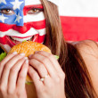 American woman eating hamburger — Stock Photo