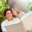 Couple reading outdoors — Stockfoto