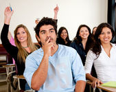 Students in a classroom rising hands — Stock Photo