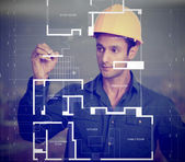 Construction worker sketching blueprints — Stockfoto