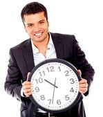 Homme d'affaires détenant une horloge — Photo