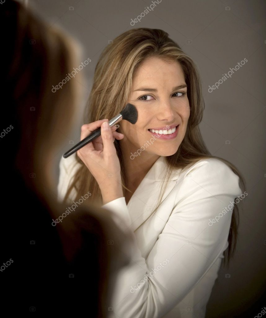 Woman putting blush on her cheeks - make up concepts — Stock Photo #10597086