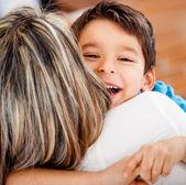 Chłopiec szczęśliwy tulenie jego matka — Zdjęcie stockowe