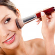 Woman applying rouge - Stockfoto