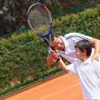 Stock Photo: Father and son playing tennis