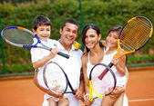 Family playing tennis — Stockfoto