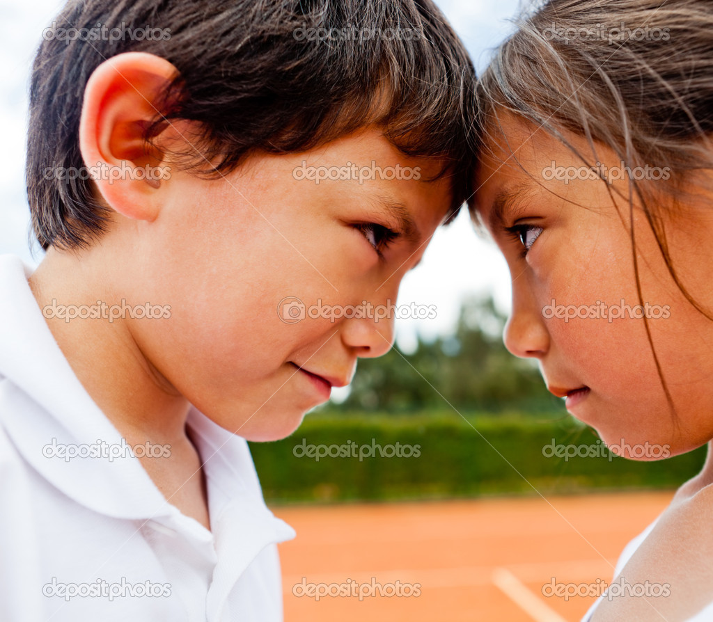 Siblings rivalry - two kids at the tennis court looking competitive — Stock Photo #8832362