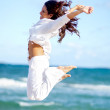 Woman at the beach jumping — Stock Photo