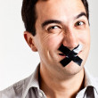 Man struggling to keep quiet - Stock Photo