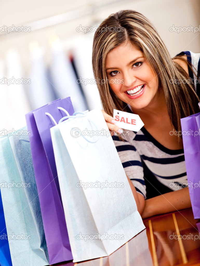 Happy shopping woman holding a sale tag  Stock Photo #8849414