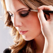 Woman putting make-up - Stock Photo