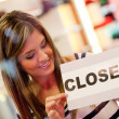 Woman closing a retail store - Stock Photo
