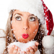 Female Santa blowing snow — Stock Photo