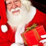 Santa with a Christmas gift — Stock Photo