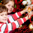 Decorating a Christmas tree - Stock fotografie