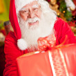 Santa with a Christmas present — Stock Photo