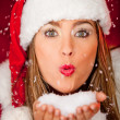 Stock Photo: Mrs Claus blowing snow
