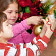 Kids hanging Christmas ball - Foto Stock