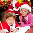 Children writing a Christmas letter — Stok fotoğraf