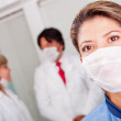 Female doctor with facemask - Stock Photo