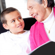 Grandmother reading to grandson - Stock Photo