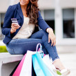 Shopping woman texting on her phone — Stock Photo
