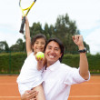 Stock Photo: Father and daughter at the tennis court