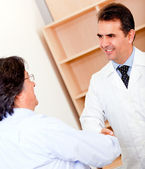 Pharmacist and business man handshaking — Stock Photo
