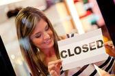 Mujer cerrando una tienda por menor — Foto de Stock