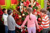 Kids around Christmas tree — Stock Photo