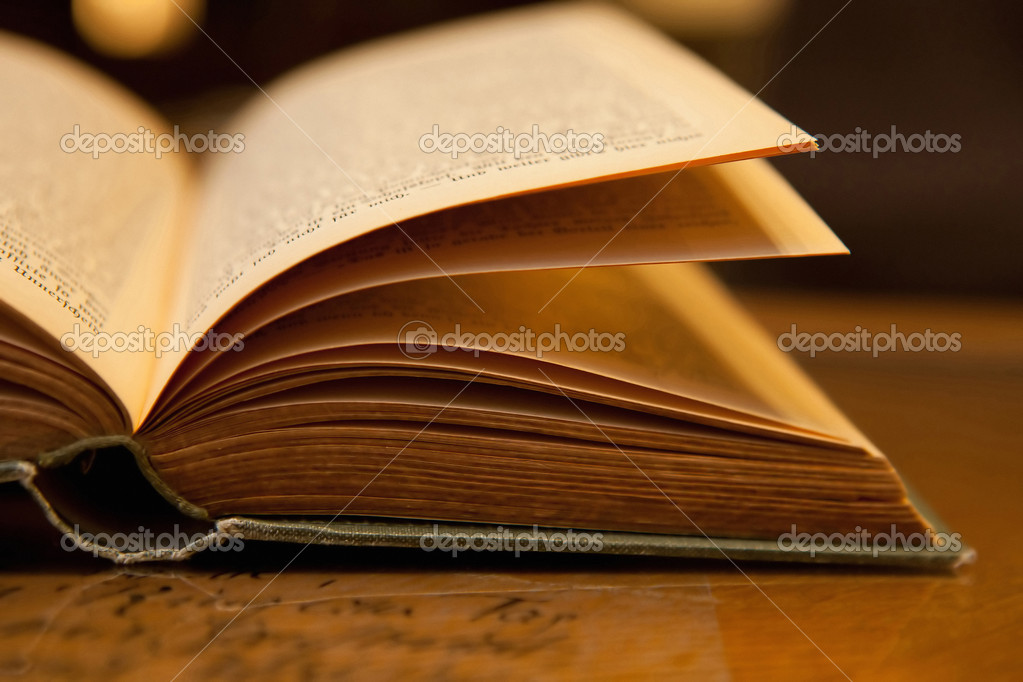 Open old book with warm light on a table  Stock Photo #8850330