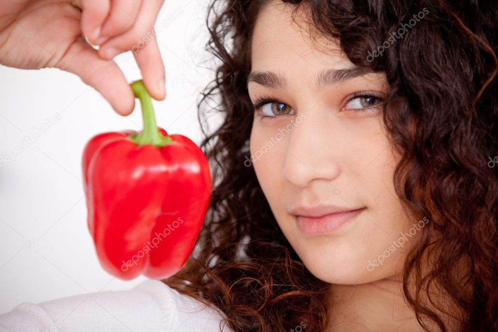 Healthy eating woman holding a red pepper  isolated over a white background  Stock Photo #8850494