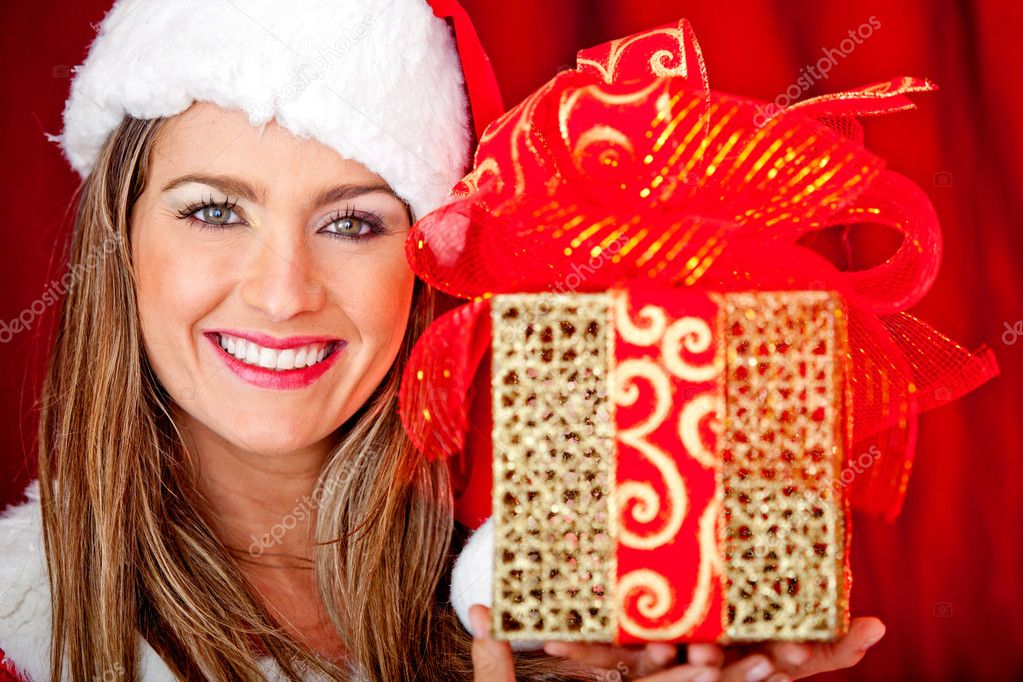 Gorgeous Mrs. Claus celebrating Christmas and holding a present — Stock Photo #8850698