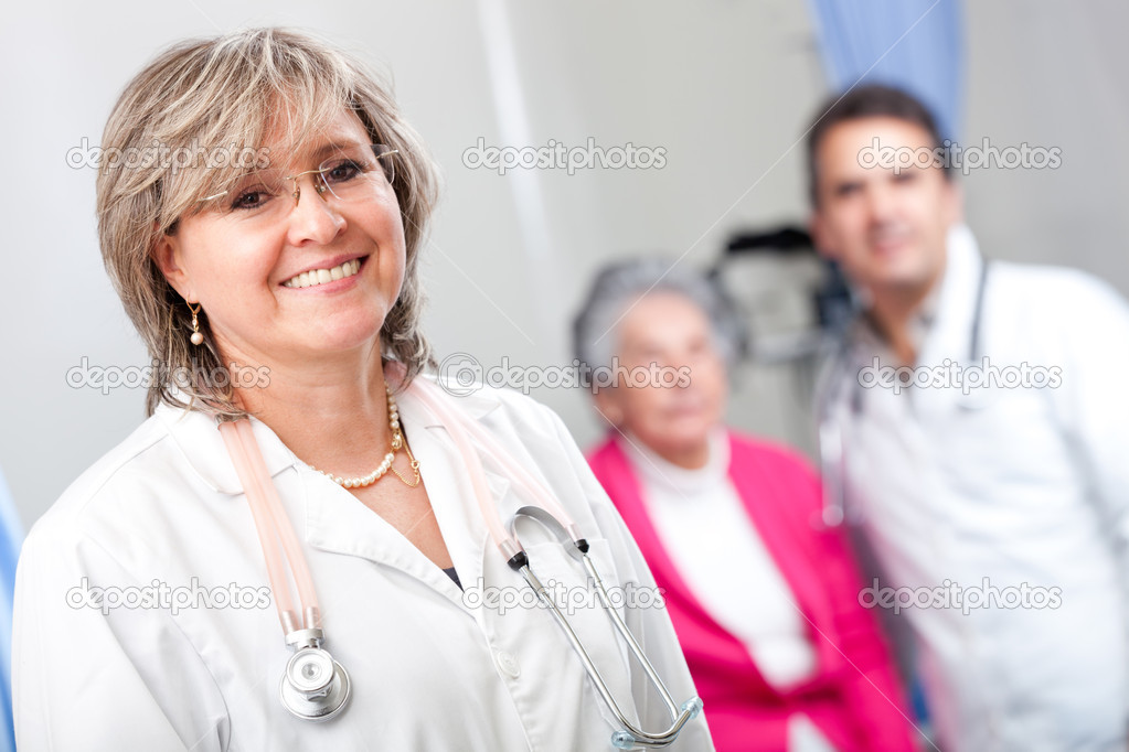 Geriatric female doctor smiling with an elder patient at the hospital — Stock Photo #8851432