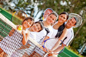 Tennis familie door het net — Stockfoto