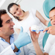 Dentist showing to brush teeth - Stock Photo