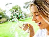 Vrouw waait bubbels — Stockfoto