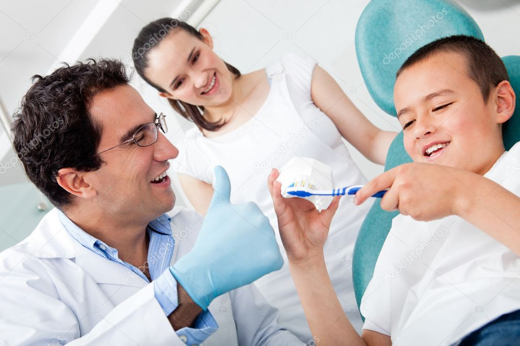 Dentist showing a boy how to brush his teeth properly — Stock Photo #9023956